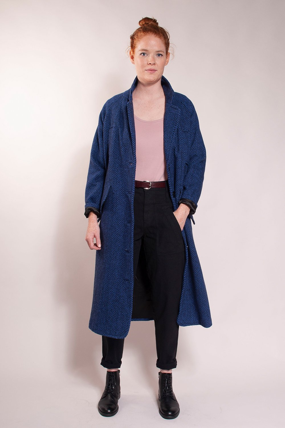 50% Wool/ 50% Polyester -- Fully lined.  Long overcoat, loose fit, welt chest handwarmer pockets and hidden button hip pockets. Great mid-weight coat!