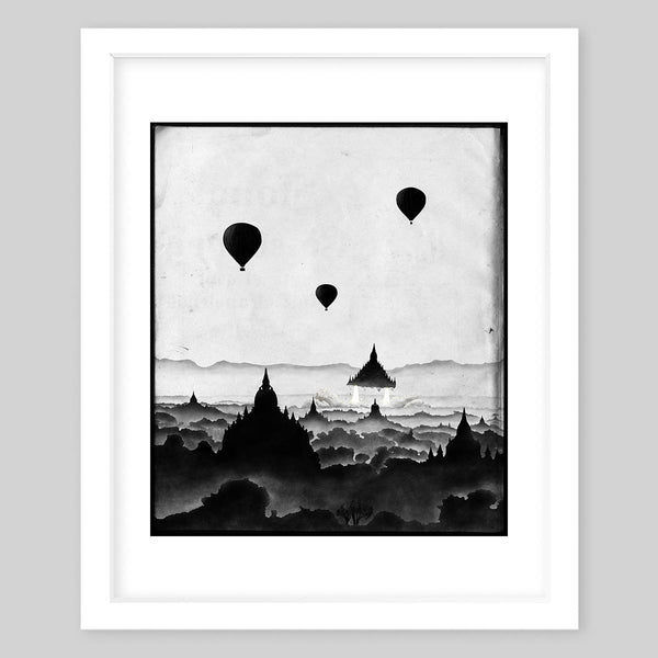 White framed art print illustrating a town and an ascending space ship all in black & white