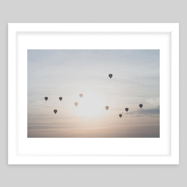 White framed art print of a photograph taken of the sky with several balloons in the air