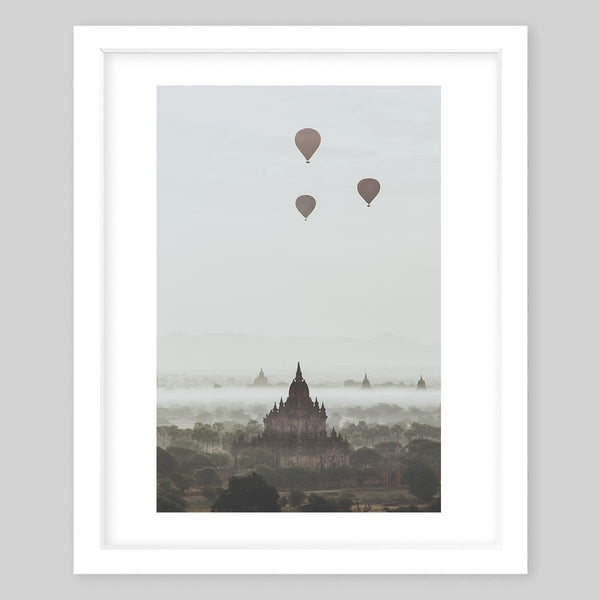 White framed art print of a photograph taken of a town with balloons in the sky and a temple in the distance