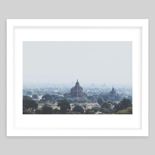 White framed art print of a photograph taken of an overview of a town with a temple in the distance