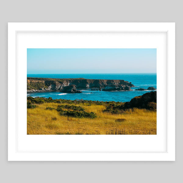 White framed art print of a photograph taken of the landscape of a beautiful blue ocean