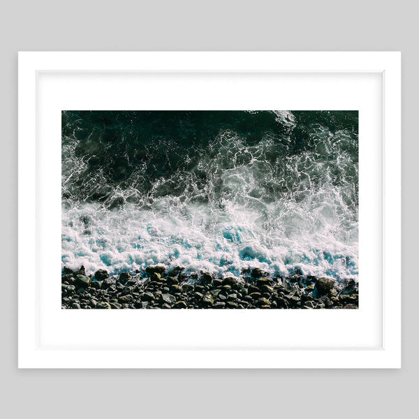 White framed art print of a photograph taken of waves crashing onto the pebbles of a shore