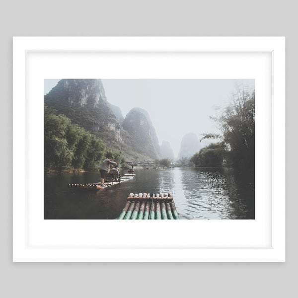 White framed art print of a photograph of a river in China with a man on a raft and surrounded by trees
