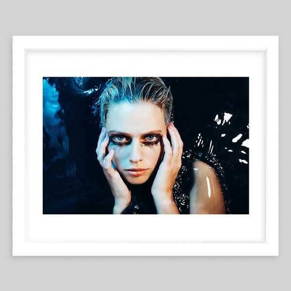 White framed art print of a photograph featuring a woman with dark eye make-up facing upwards as she lays in dark water and has her hands on her cheeks