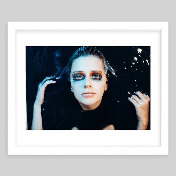 White framed art print of a photograph featuring a woman with dark eye make-up facing upwards as she lays in dark water