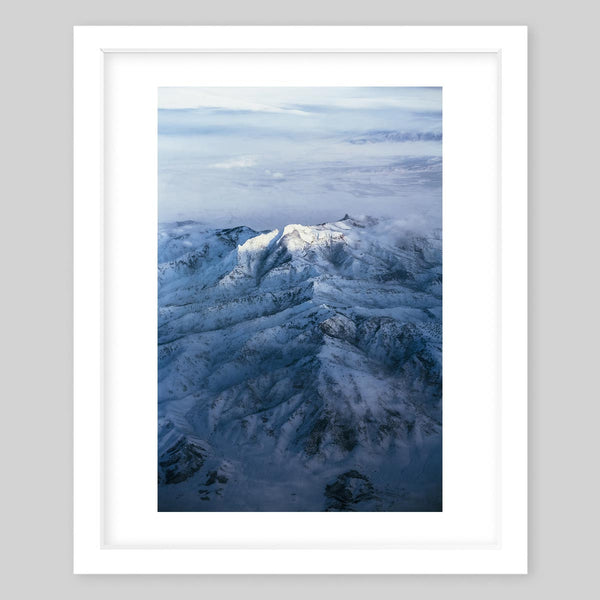 White framed art print of a photograph of mountains covered in snow and white clouds in the background