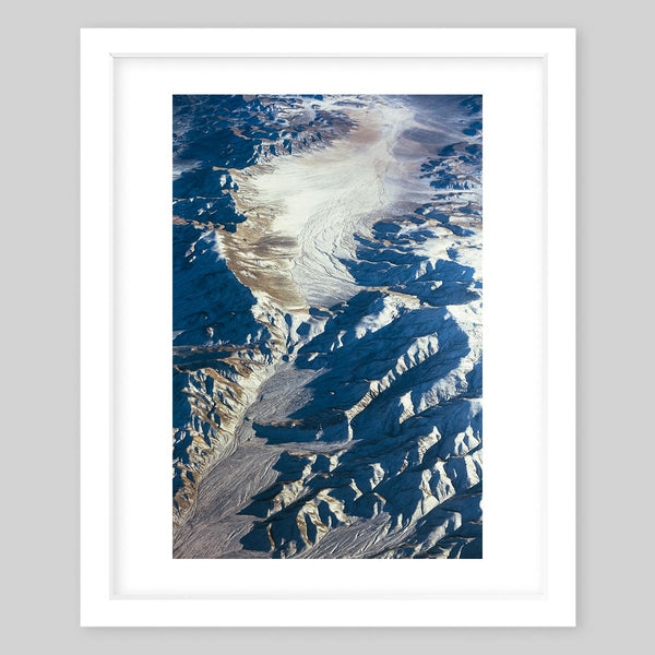 White framed art print of a photograph of rock erosion a trail