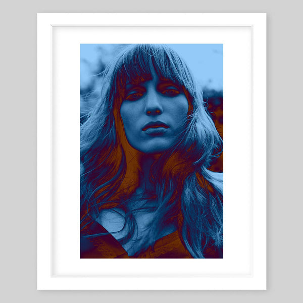 White framed art print of a photograph portrait of a woman with fierce attitude in a blue hue