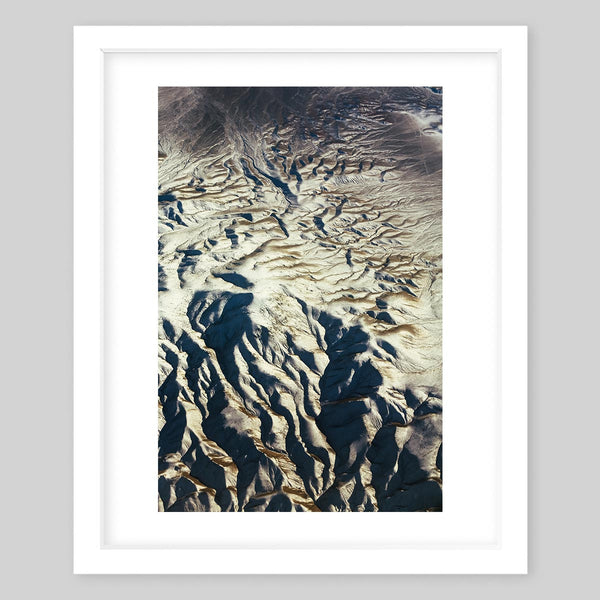 White framed art print of a photograph of sand dunes or a rock wall