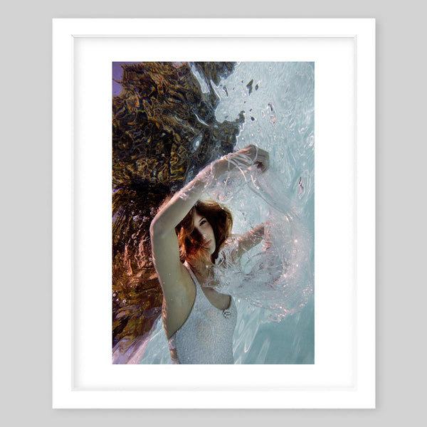 White framed art print of a photograph of a woman with long brown hair under water in white garments
