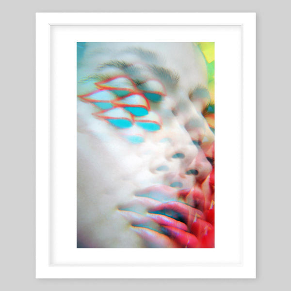 White framed art print of the photograph of the portrait of a woman with a kaleidoscope effect and hints of neon color on the corners of the portrait