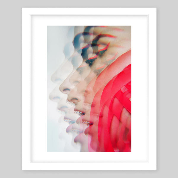 White framed art print of a photograph of a woman's side profile with kaleidoscope effects and accents of bright red makeup and details