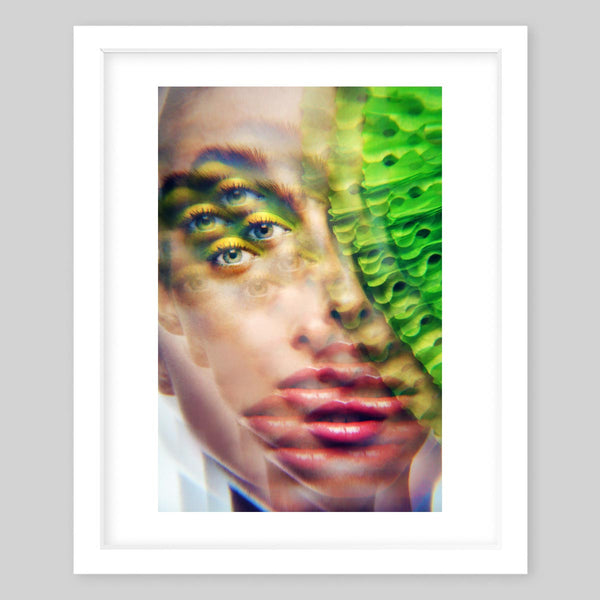 White framed art print of the photograph of a woman with neon makeup all in a kaleidoscope effect