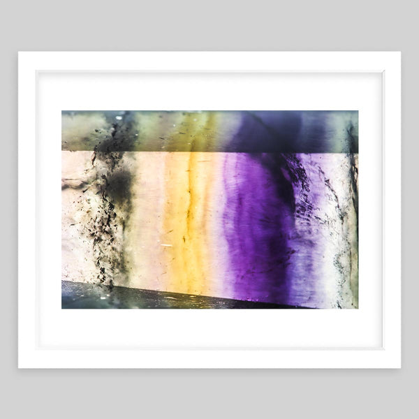 White framed art print of a photograph of a rock wall with purple and yellow lighting
