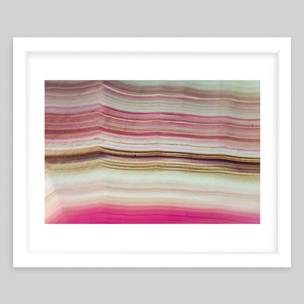 White framed art print of a photograph of a striped pattern with pink and cream colors