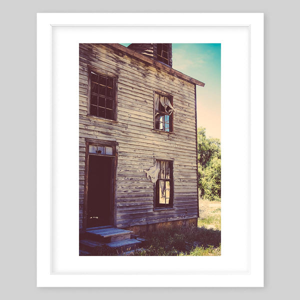 White framed art print of a photograph of the front view of an abandoned rustic home
