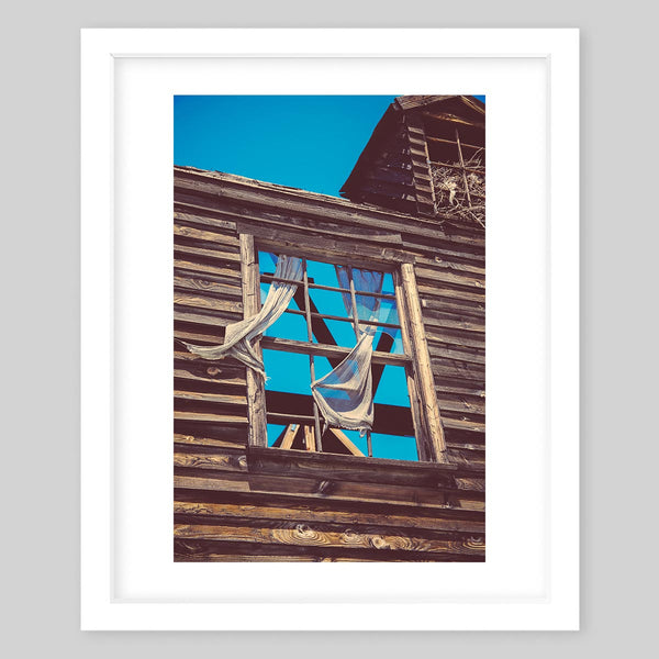 White framed art print of a photograph of the glass-less window of an old, rustic abandoned house