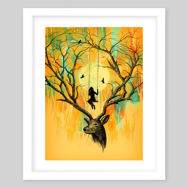 White framed art print of a deer who's antlers resemble tree branches, there is a silhouette of a girl on a swing and tow birds in between the two antlers