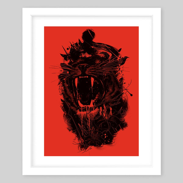 White framed art print of a bright red background with a growling lion surrounded by nature in the center