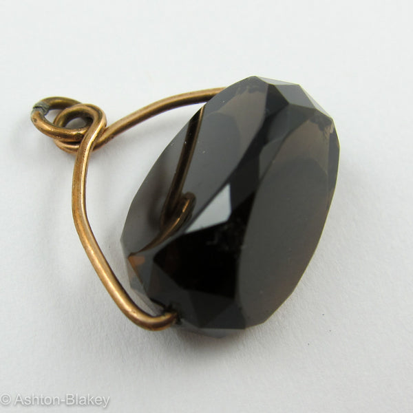 FOB Smoky topaz roller stone held by 9K pink gold holder