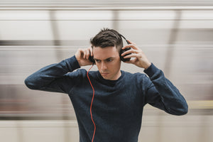 A man listening to music on headphones with a blurred bakcground