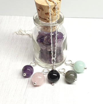 Interchangeable gemstone pendant set with amethyst, rose quartz, black tourmaline, labradorite, and amazonite.