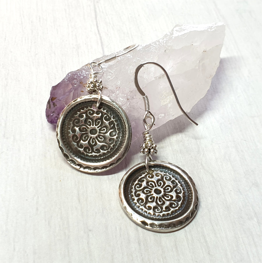 Silver boho style mandala earrings.