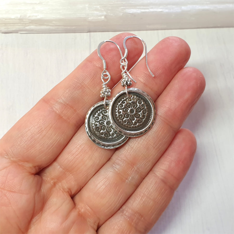 Dangling silver mandala earrings.