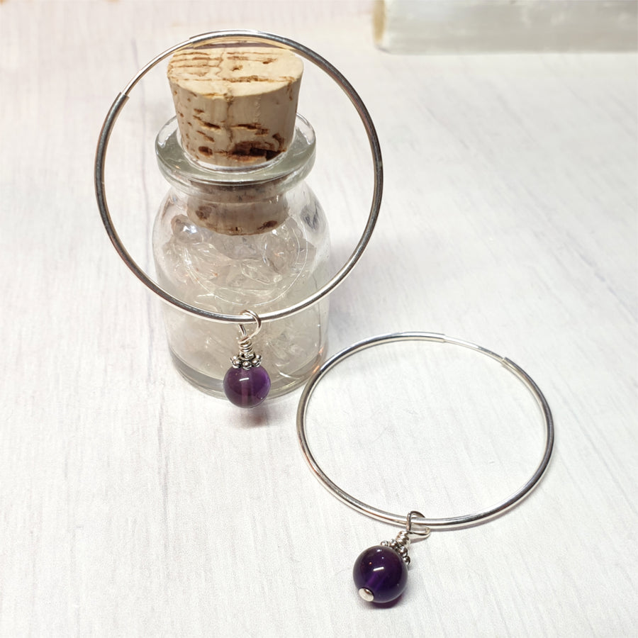 Sterling silver hoop earrings with amethyst dangles.