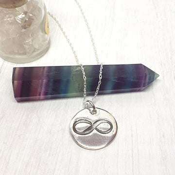 Silver infinity medallion necklace.