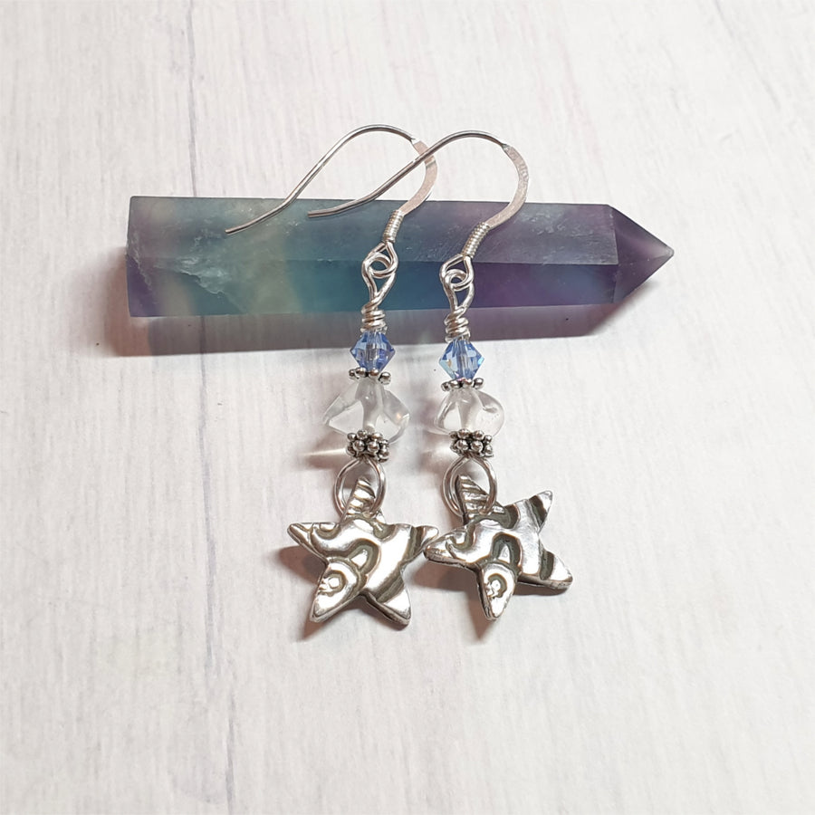 Shimmering sterling silver star earrings with blue crystals and clear quartz.