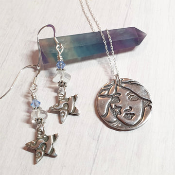 A whimsical silver necklace set with a star woman pendant and star shaped earrings.