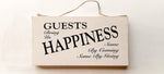 wood sign saying Guests Bring Us Happiness, Some by Coming, Some By Going