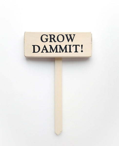 wood sign saying Grow Dammit!