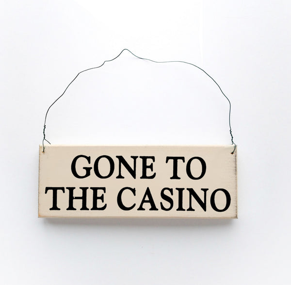 wood sign saying Gone to The Casino