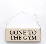 wood sign saying Gone to the Gym