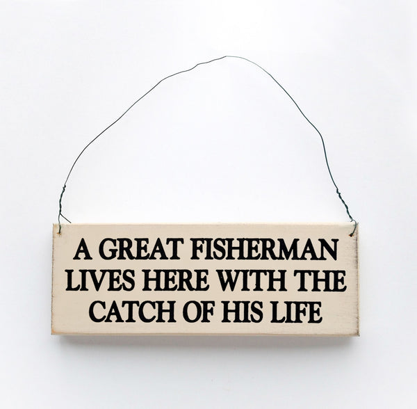 wood sign saying A Great Fisherman Lives Here With The Catch of His Life