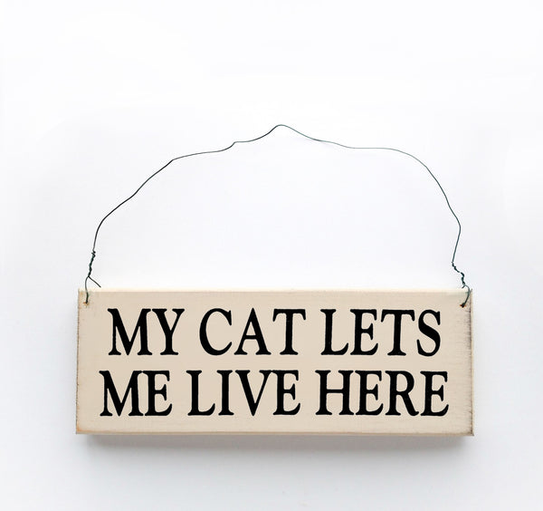 wood sign saying My Cat Lets Me Live Here