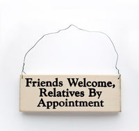 wood sign saying Friends Welcome, Relatives By Appointment