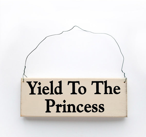 wood sign saying Yield to the Princess