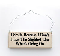 wood sign saying I Smile Because I Don't Have the Slightest Idea What's Going On