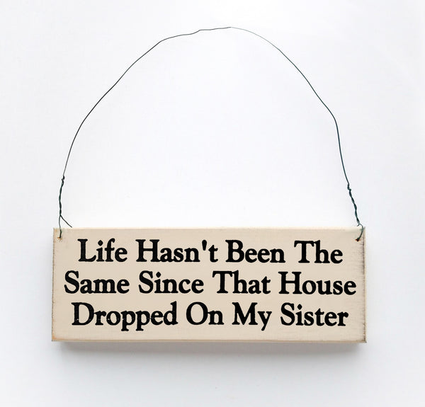 wood sign saying Life Hasn't Been the Same Since That House Dropped On My Sister