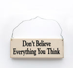 wood sign saying Don't Believe Everything You Think
