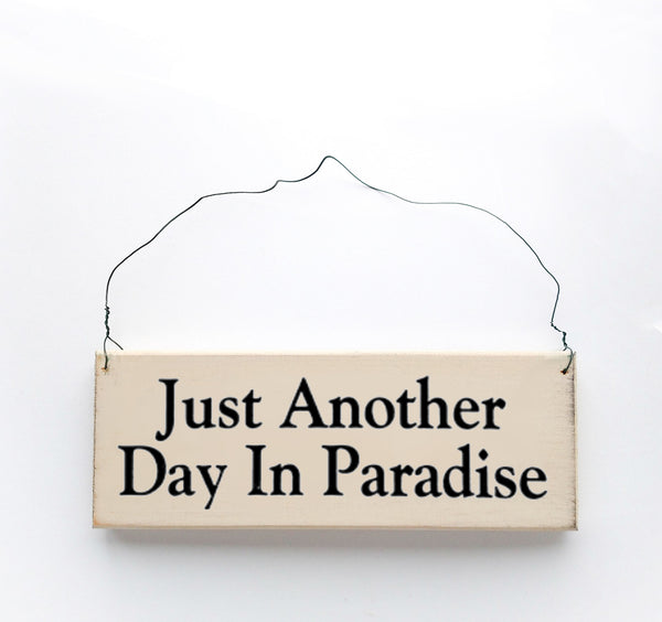 wood sign saying Just Another Day In Paradise