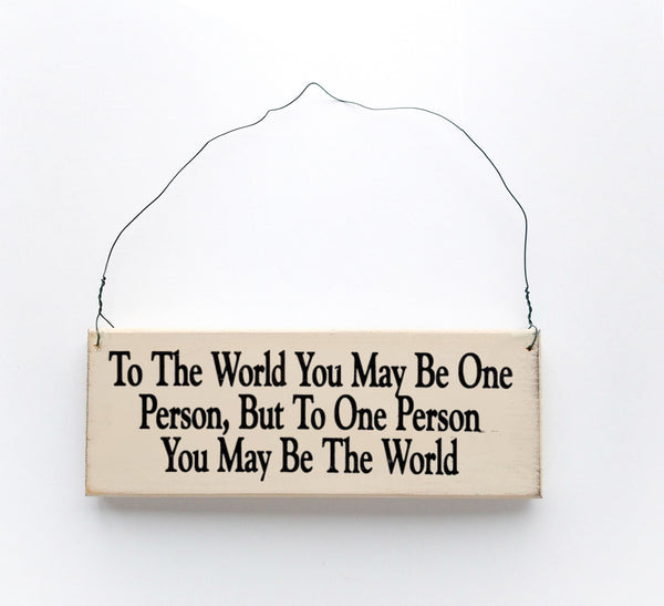 wood sign saying To the World, You May Be One Person, But To One Person You May Be The World