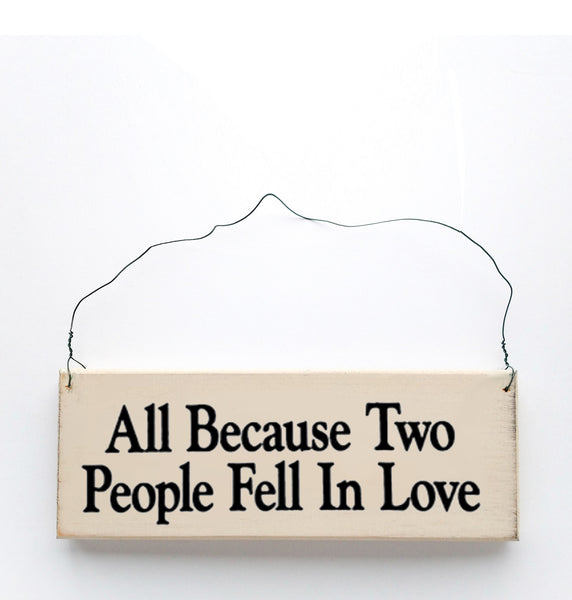 wood sign saying All Because Two People Fell In Love