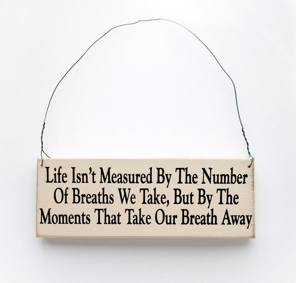 wood sign saying Life Isn't Measured By The Number of Breaths we Take, But By The Moments That Take Our Breath Away