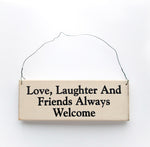 wood sign saying Love, Laughter and Friends Always Welcome