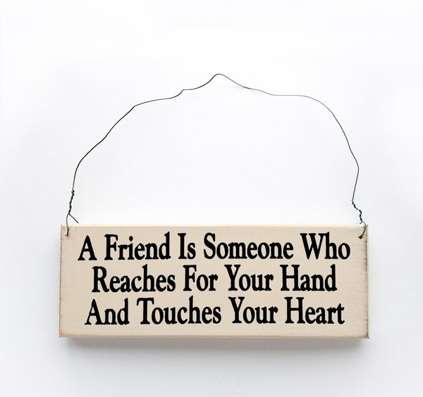 wood sign saying A Friend is Someone Who Reaches for Your Hand and Touches Your Heart